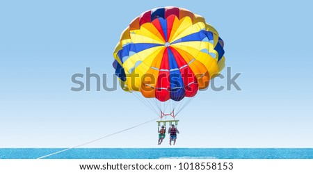 Happy couple Parasailing on Tropical Beach in summer. Couple under parachute hanging mid air. Having fun. Tropical Paradise. Positive human emotions, feelings, family, travel, vacation. #1018558153