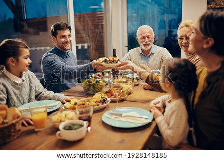 Happy couple passing food while having family lunch in dining room.