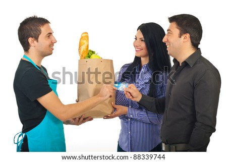Happy couple paying by credit card their food at grocery to a salesperson man in blue apron isolated on white background