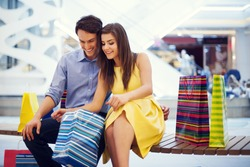 Happy couple peeking into shopping bag