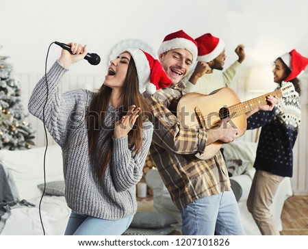 Happy couple playing on guitar and singing Christmas song at house party, copy space