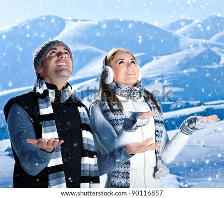 Happy couple playing outdoor at winter mountains, active people over natural blue wintertime landscape background with falling snow, Christmas vacation holidays