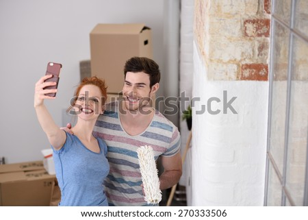 Happy couple posing for a selfie in their new home standing close together with a paint roller alongside an unfinished white wall