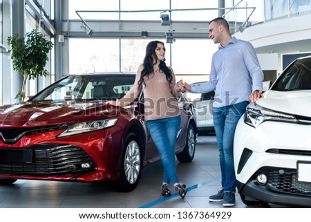 Happy couple posing with new cars in showroom #1367364929