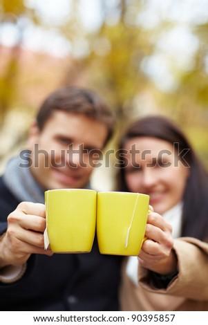 Happy couple raising glasses with hot tea in autumn