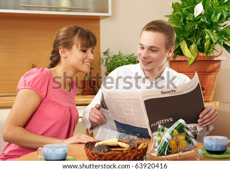 Happy couple reading paper while sitting in the kitchen