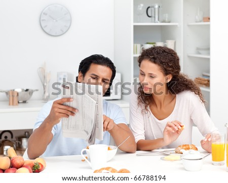 Happy couple reading the newspaper together during breakfast at home