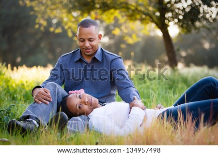 Happy couple relaxing in a grassy field