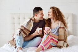 Happy couple relaxing in bed with hot beverage, holds cups full of tea or coffee, sit under warm blanket, dresses casually, romantic young family, spend spare time together at home. Relation concept.