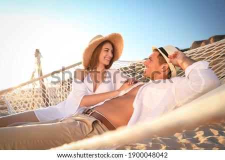 Happy couple relaxing in hammock on beach Stock foto ©