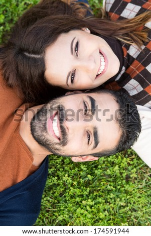 Happy couple relaxing on the grass park stock photo