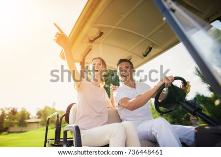 Happy couple riding a golf cart. A man in a white suit is sitting at the wheel and driving a golf car, a woman in a light suit is sitting beside him #736448461