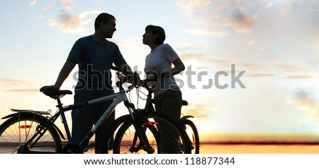 Happy couple riding bicycles outside, healthy lifestyle fun conc