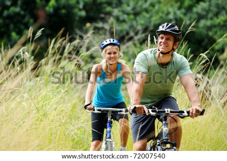 Happy couple riding bicycles outside healthy lifestyle fun concept