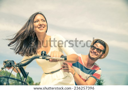 Happy couple riding bikes in the city - Young pretty woman driving bicycle and playful man sitting behind - Portrait of two lovers outdoors