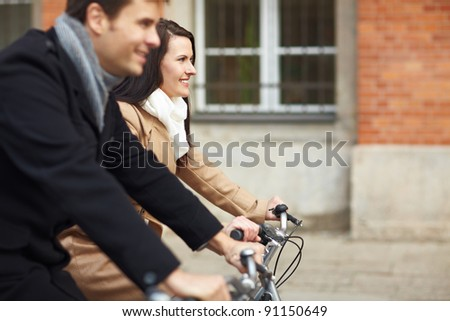 Happy couple riding bikes together in a city