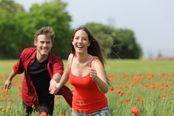Happy couple running and flirting between the grass on a green poppy field in spring