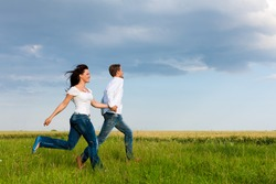 Happy couple running on a dirt road in summer holding hands