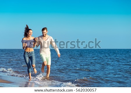 happy couple running on the beach #562030057