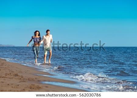 happy couple running on the beach #562030786