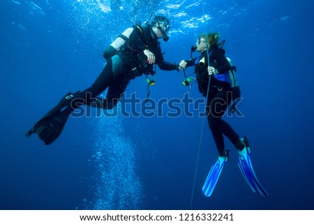 Happy couple scuba divers hovering together on a safety stop  #1216332241