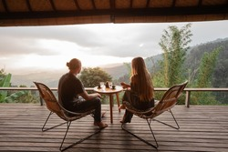 Happy couple sit on wicker chairs at outdoor terrace in the mountains and drink wine. Romantic time together