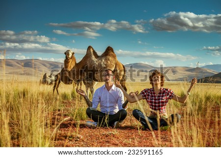 Happy couple sits in lotus position on the background of a big camel