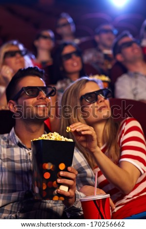 Happy couple sitting in auditorium of 3D movie, eating popcorn.