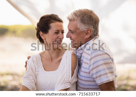 Happy couple sitting in cottage during safari vacation