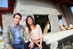 Happy couple sitting in front of house under construction