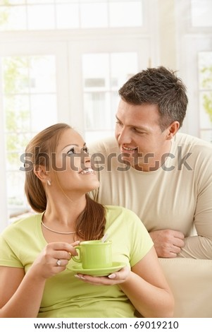 Happy couple sitting in living room, woman holding tea cup with two hands looking up at man smiling.? - stock photo