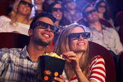 Happy couple sitting in movie theater, watching 3D movie, eating popcorn, smiling.