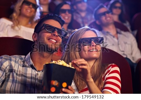 Photo of  Happy couple sitting in movie theater, watching 3D movie, eating popcorn, smiling.