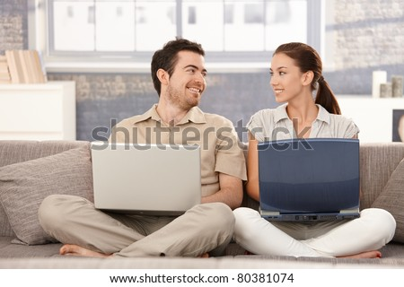 Happy couple sitting on sofa at home, browsing internet on separate laptops, smiling, having fun.?