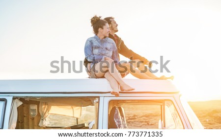 Happy couple sitting on top of minivan roof at sunset - Young people having fun on spring vacation traveling around the world - Travel,love and holiday concept - Focus on faces