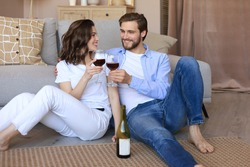 Happy couple sitting, relaxing on floor in living room, drinking red wine. Smiling young husband and wife rest at home enjoy romantic date on family weekend together