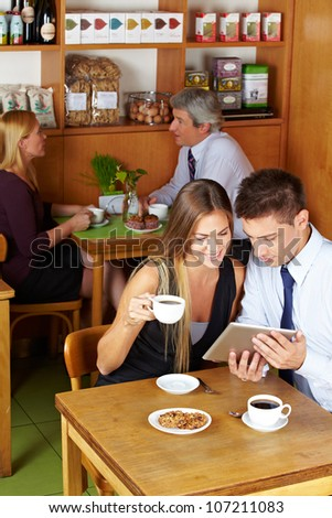Happy couple sitting with a tablet computer in a caf�©