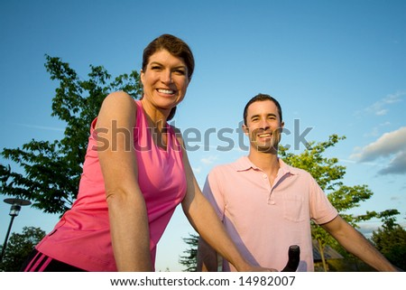 Happy couple smiling as they stand by their bikes. Horizontally framed photograph