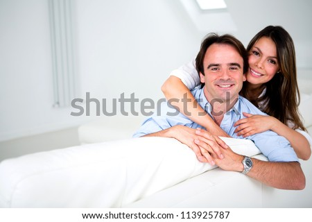 Happy couple smiling at home and hugging