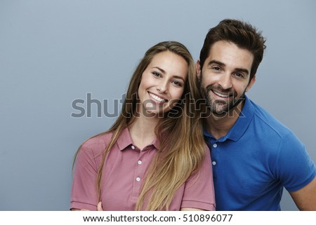 Happy couple smiling in polo shirts, portrait
