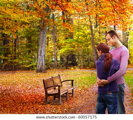 Happy couple standing embraced in the autumnal park looking to a bench