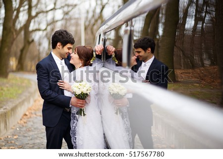 happy couple standing near long white limousine