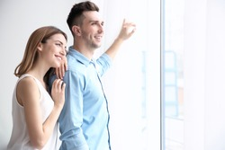 Happy couple standing near window and opening curtains