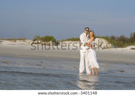 Happy couple standing on a beach, looking towards the ocean.