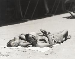 Happy couple sunbathing on beach