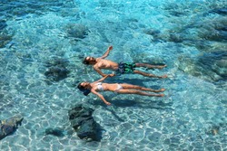 Happy couple swimming in the transparent turquoise sea. Tropical vacation and honeymoon concept. Top view of