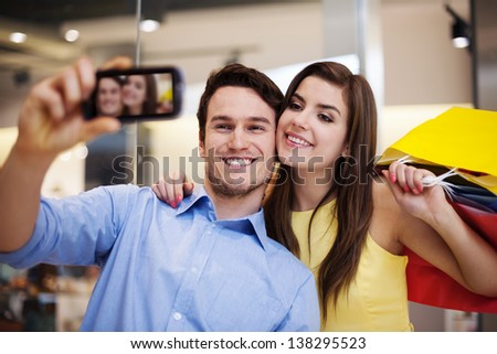 Happy couple taking a photo in the shopping mall