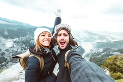 Happy couple taking a selfie hiking mountains - Successful hikers on the top of the peak smiling at camera