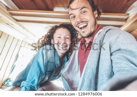 Happy couple taking a selfie in mini van camper during a roadtrip - Travel people having fun making pictures with mobile phone in vintage minivan - Relationship, vacation and youth lifestyle concept
