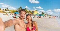 Happy couple taking fun selfie on Florida beach on travel summer vacation. Suntan man and Asian bikini woman in bikini using phone laughing POV. Interracial group portrait on Fort Myers beach holiday.